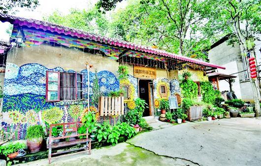 图为东湖风景区大李文创村一处民宿外部装点着花草,涂鸦等,显得既自然