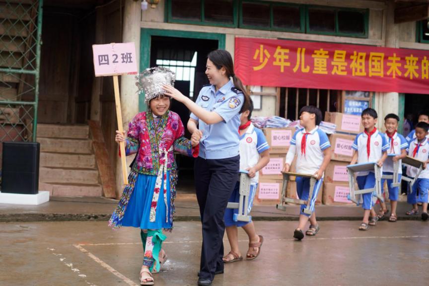 民警与穿着苗族服饰的学生们亮相六一儿童节