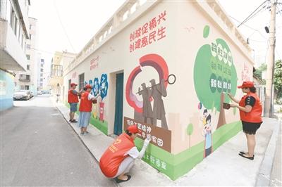 笃工街道人民里社区志愿者绘制墙画美化园区环境。