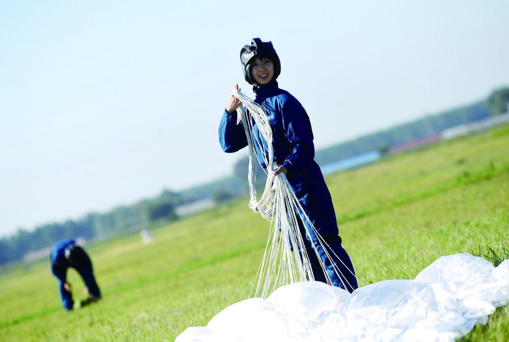 第一个落地的女学员温世敏,面带笑容整理降落伞,显得非常轻松。