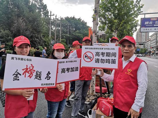 年近花甲的黄飞华(右一)就带着团队中的10名成员来到了杭州高级中学考点,进行爱心助考服务。  童笑雨摄