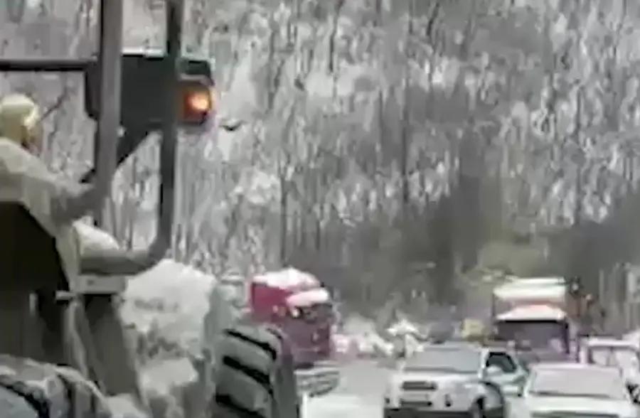 秦岭积雪致30余辆危化品车滞留 交警司机同铲雪