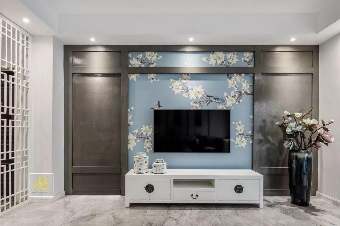 中间摆一张白色中式电视柜,背景墙则是贴着花鸟图案的墙纸,营造出一种