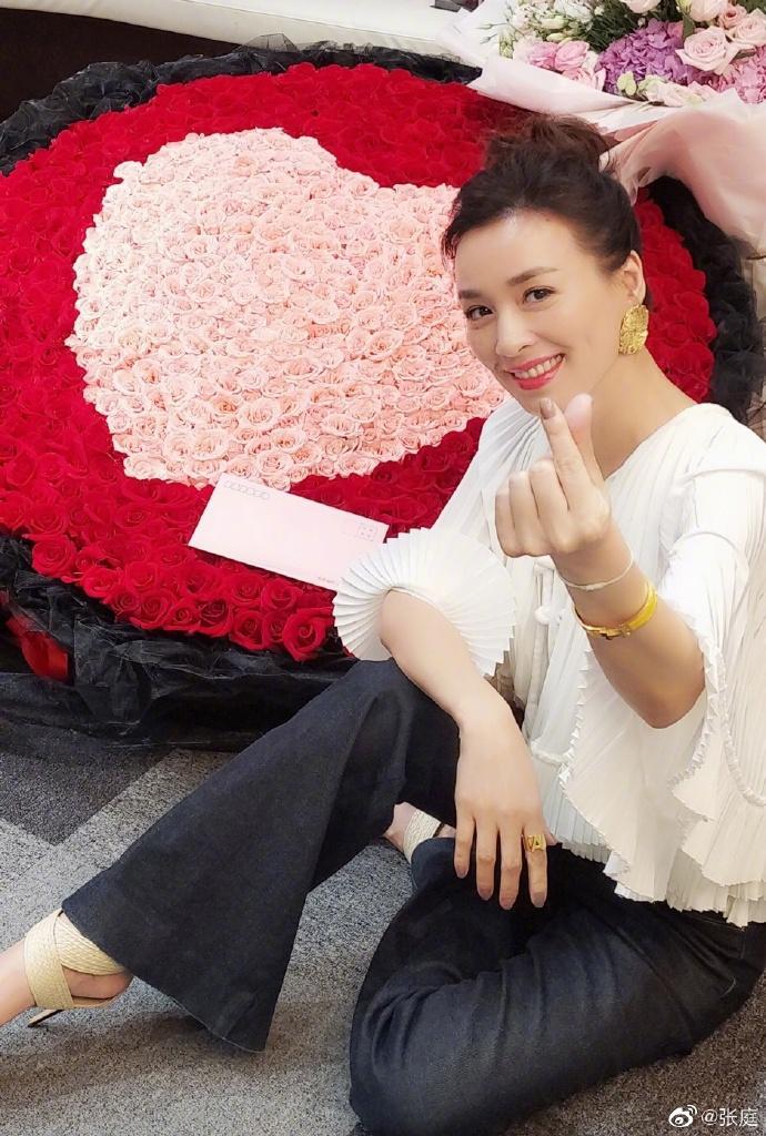 49岁张庭七夕晒照,身后巨型玫瑰花束抢眼,结婚13年依然浪漫恩爱