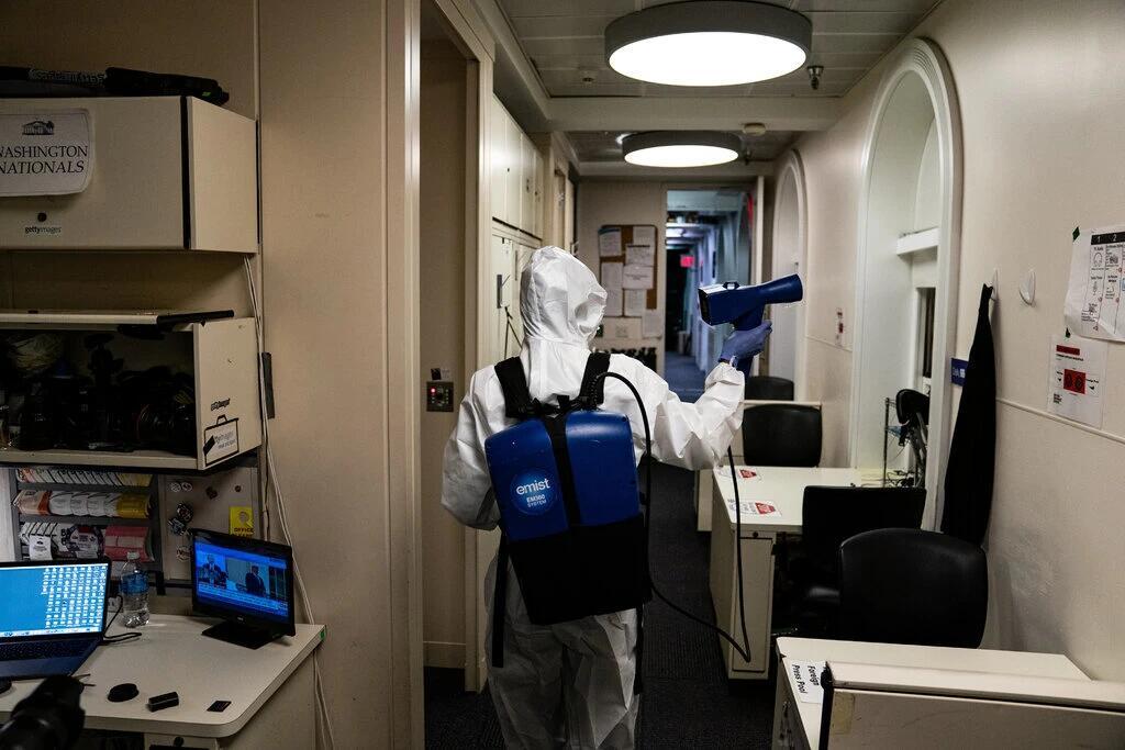 (本周,包括简报室在内的白宫部分地区就像是一个危险区域。身着全套防护服的工作人员在对公共场所进行消毒。图源:《纽约时报》)