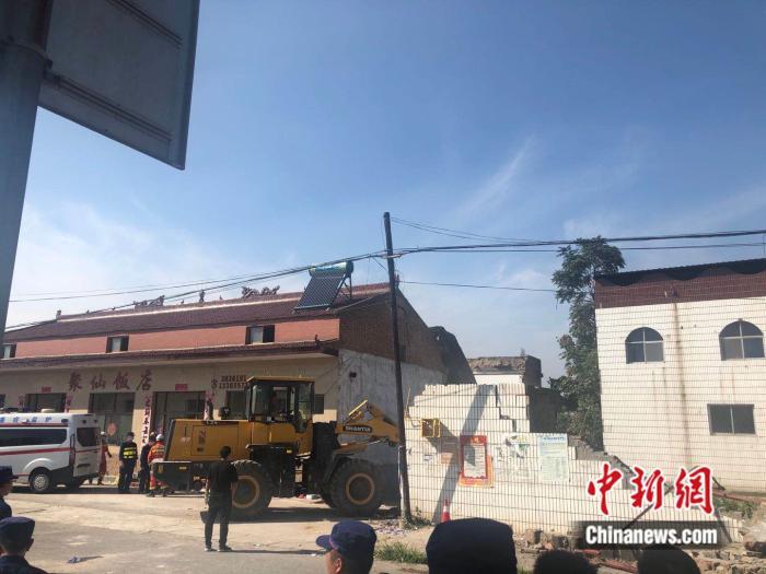 武警、消防等力量正持续救援,救护车辆在聚仙饭店门口等候。李庭耀 摄