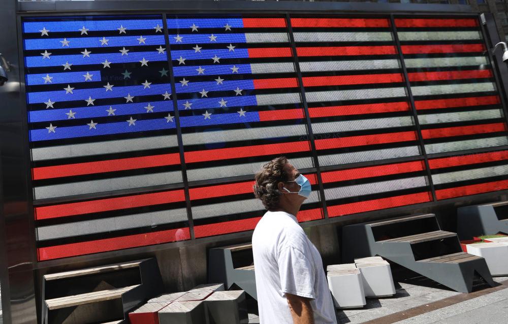 ▲7月23日,在美国纽约时报广场,一名戴口罩的行人走在街头。(新华社记者 王迎 摄)