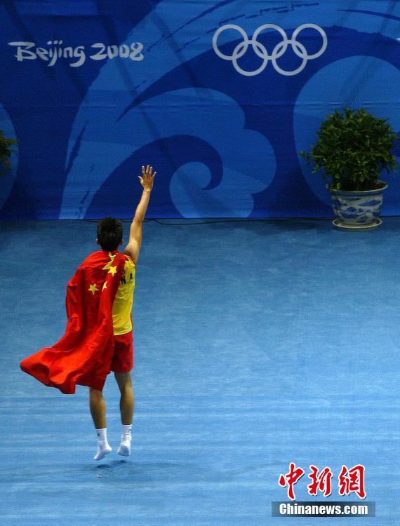 2008年8月17日,北京工业大学体育馆,2008北京奥运会,羽毛球男单决赛,林丹获得男单冠军后披国旗庆祝。图片来源:视觉中国