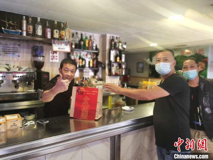 侨领将中秋月饼送到侨胞手中。 浙江省侨联供图 摄