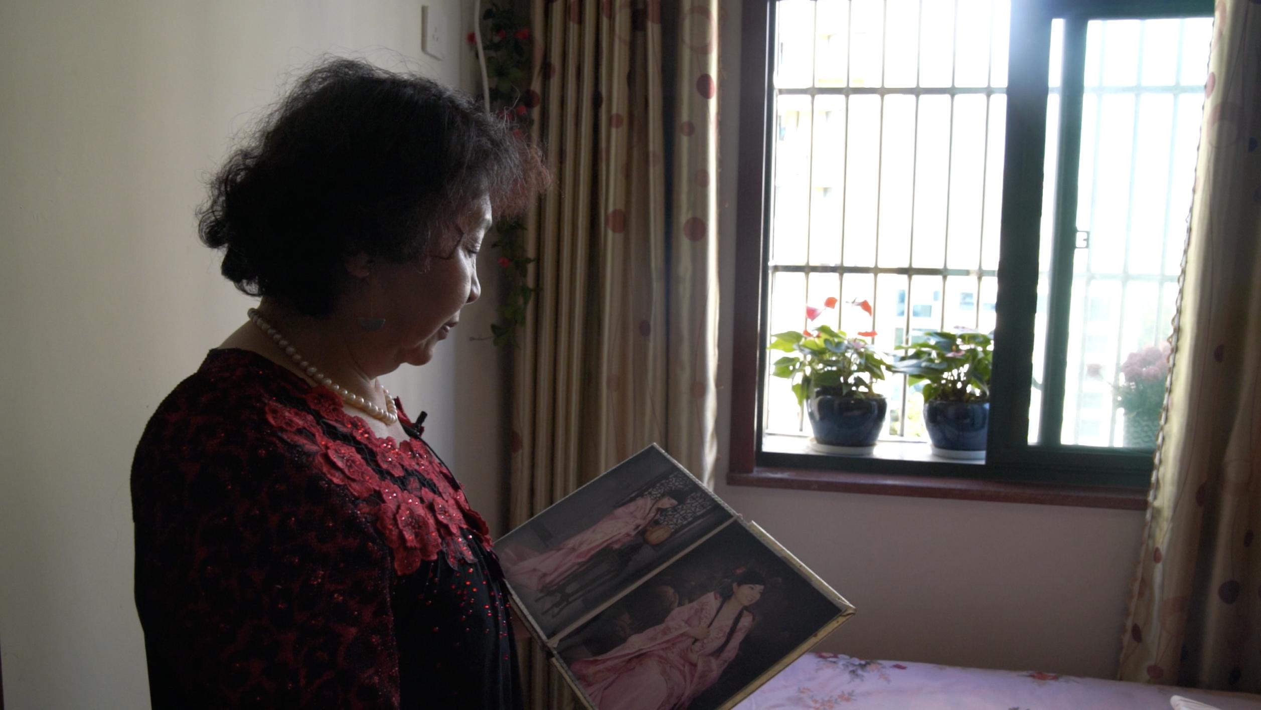 盛海琳在看女儿婷婷的照片。来源:视频截图