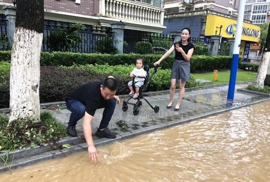图为利万物流公司总经理杨松岭正在帮忙疏通下水道。 宁波大榭开发区供图