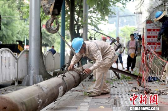 """国网三明供电公司将""""e三明""""APP上群众所反映的影响路人出行的路边电杆拆除。 吴学生摄"""