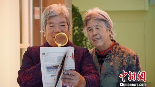 """图为社区居民从""""便民服务柜""""借放大镜看报纸。 魏建军摄"""