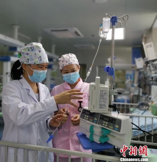 8月18日,莫晓燕医生查看病儿输液情况。 张超群摄