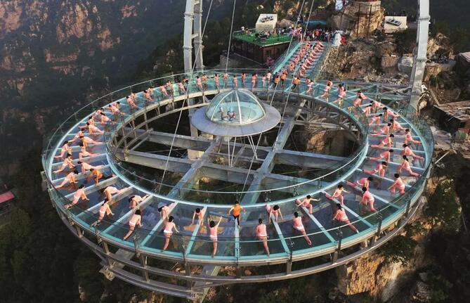 2016年6月19日,150余名瑜伽爱好者在北京平谷石林峡景区海拔700多米高的钛合金玻璃观景平台上练瑜伽。摄影/中国新闻周刊记者富田