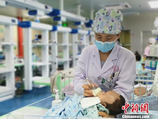 8月18日,莫晓燕医生给患儿喂奶。 张超群摄