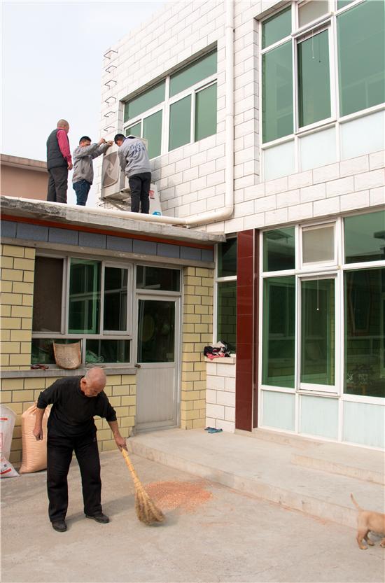 袁庄村一户村民家里设备制热效果差,王国良与同事张亮爬上屋顶抢修。
