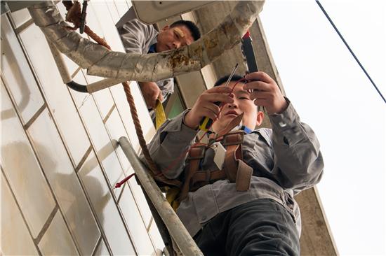 △11月18日,王国良与同事张宝兰在北京房山区窦店镇袁庄村一户村民家里检修供暖机器。