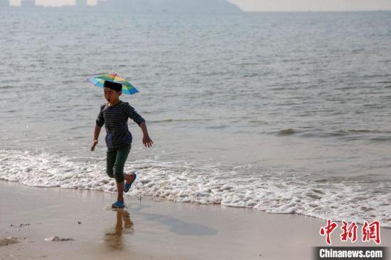 """三亚湾沙滩上,一位小朋友头戴""""伞帽""""在嬉水。(资料图) 王晓斌摄"""