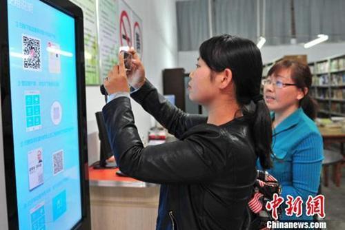 资料图:湖北省宜都市的市民在电子图书馆借阅终端上下载自己喜欢阅读的电子图书。曹礼达摄