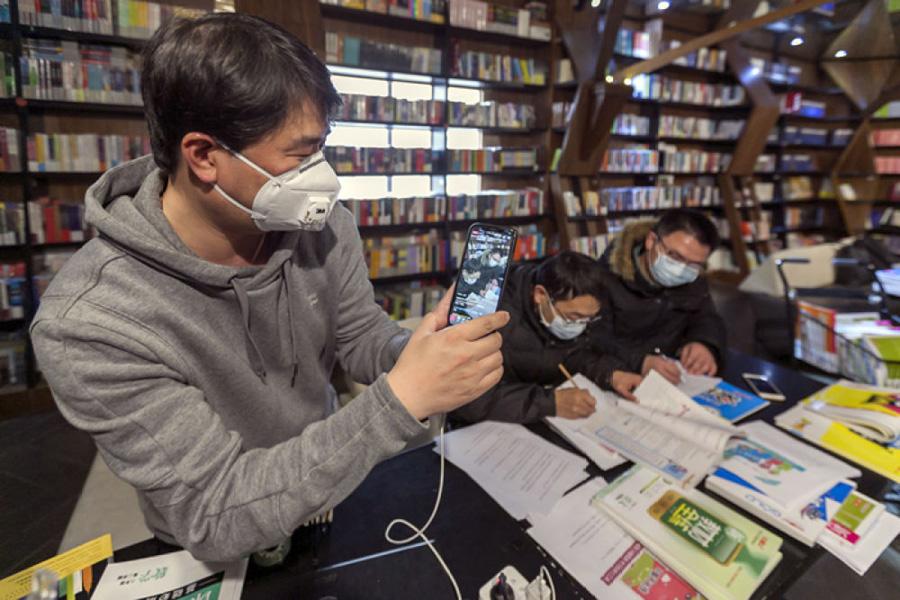 上海鍾書閣閔行店店長謝寧(左)在實體書店內通過網絡直播銷售圖書。新華社記者王翔圖