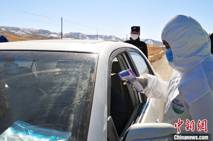 图为达久滩联防联控卡点值守人员对过往人员进行体温测量。 祁正明摄