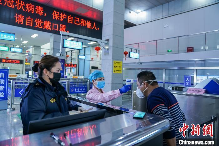 图为友谊关海关关员对通行旅客进行体温检测。 陈冠言摄
