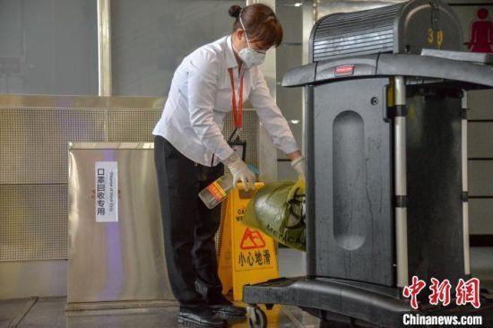 图为14日,海口美兰国际机场清洁工收集口罩后消毒。 洪坚鹏摄