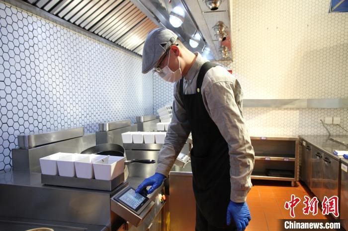 山东济南一家智慧餐厅,采用智能炒菜机器人做饭,工作人员只需操作机器,炒菜机器人在两到三分钟左右便可出餐。 孙宏瑗摄