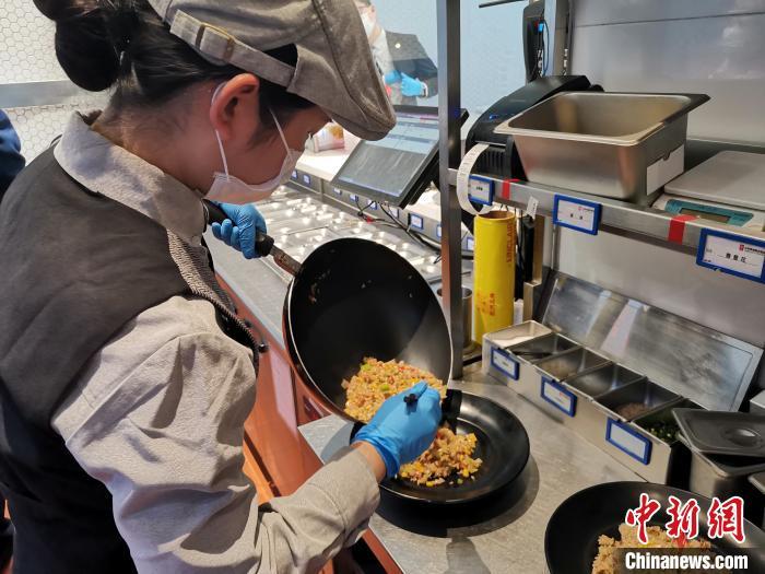 山东济南一家智慧餐厅采用智能炒菜机器人做饭,工作人员只需操作机器后,将制作好的餐食装盘,便可送上顾客餐桌。 孙宏瑗摄