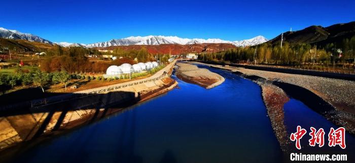 图为清澈的隆畅河静静流淌,不远处的祁连山银装素裹。 武雪峰摄