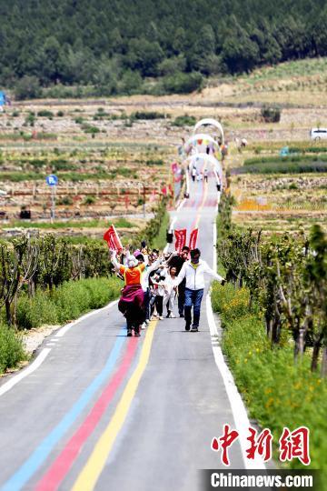 在一家玫瑰加工企业的生态产业园内,一群游客在田间道路上唱跳自如,欢呼雀跃。 沙见龙摄