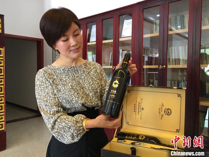 图为王玉兰向记者展示企业研发的党参葡萄酒。 张婧摄