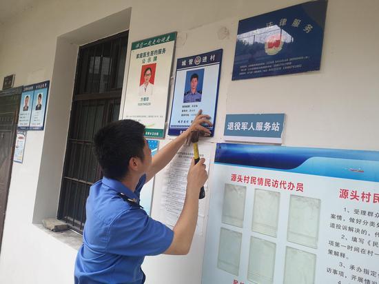 """浦江县综合行政执法局在村公开栏张贴""""一村一城管""""联系牌。 周彦摄"""