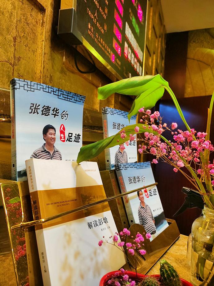 彭墩集团旗下的酒店,前台摆着宣传张德华的书。