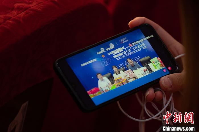大学生用手机收看直播。 泱波摄