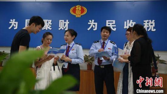 图为三亚市税务局干部为旅游业纳税人介绍政策。海南省税务局供图
