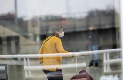 2020年3月13日,在美国纽约肯尼迪国际机场,一名旅客走在航站楼里。新华社发