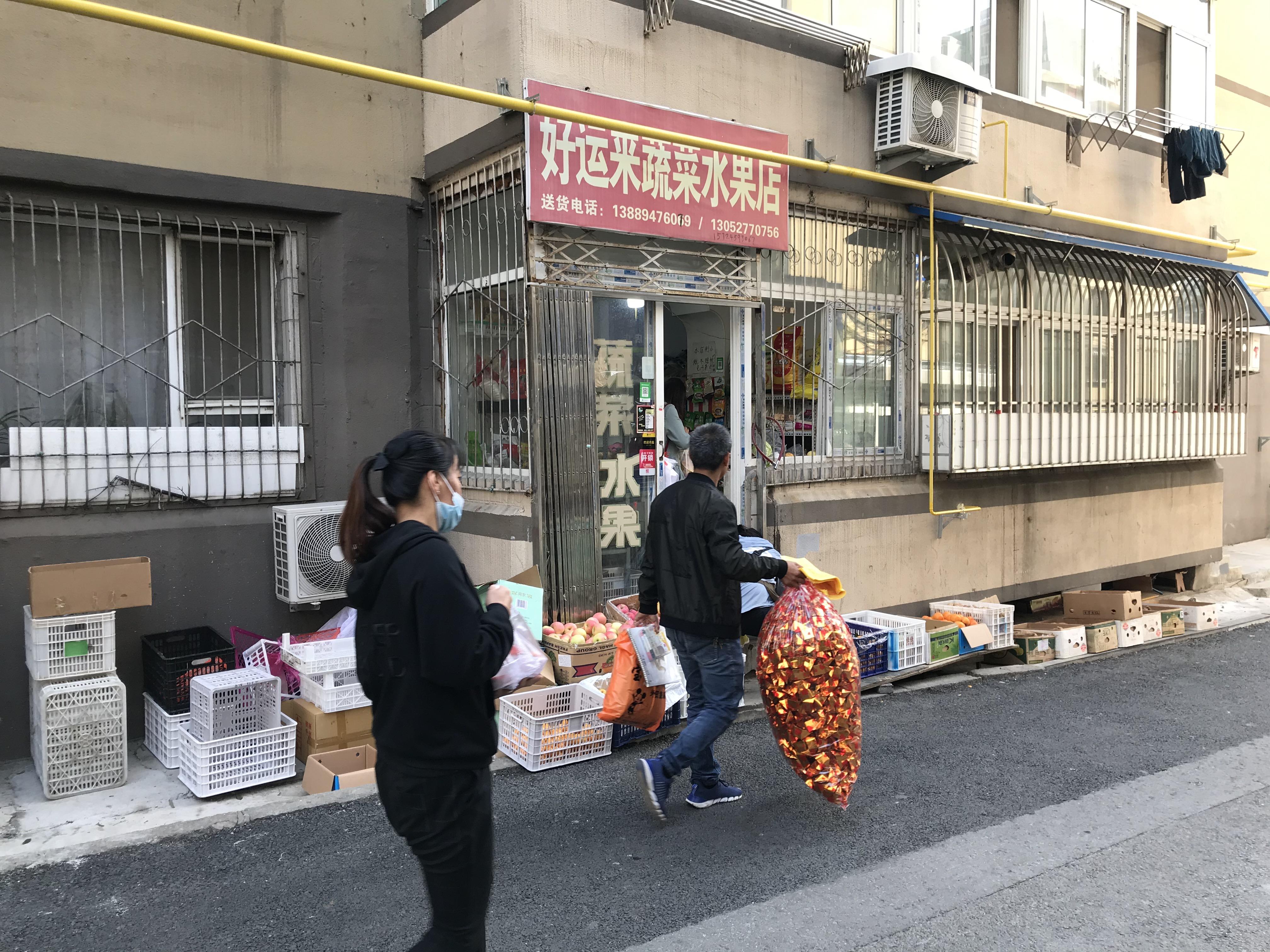 """忌日当天,夫妻俩走过""""好运来""""蔬菜水果店。澎湃新闻记者 沈文迪  图"""