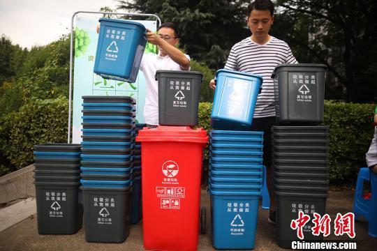 """资料图:大学生将印有""""垃圾分类,从我做起""""字样的垃圾桶摆放整齐。 泱波 摄"""