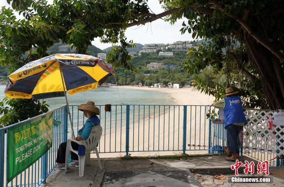 7月25日,香港深水湾泳滩已经封闭,有工作人员把守出入口。香港康乐及文化事务署当天宣布,因应新冠肺炎最新情况,康文署辖下所有泳滩已经关闭,泳滩的设施暂停开放,进入已封闭的沙滩属违法行为,一经定罪可被罚款2000港元及监禁14天。康文署呼吁市民尽量留在家中,不要前往沙滩游泳或日光浴,减低病毒在社区传播的风险。中新社记者 张炜 摄