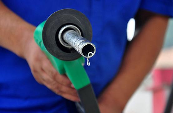 河北省承德县的一家加油站工作人员完成加油后放回油枪。图