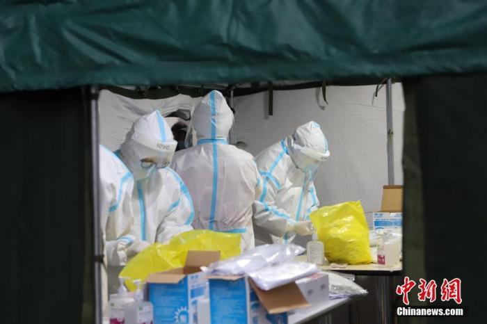 11月21日,受新冠肺炎疫情影响,天津市滨海新区对辖区内全体居民进行大规模核酸检测筛查。图为核酸检测取样现场忙碌的医务工作者。 中新社记者 张道正 摄