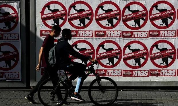 """阿根廷布宜诺斯艾利斯街头写着""""对债务偿还说不""""的海报。"""