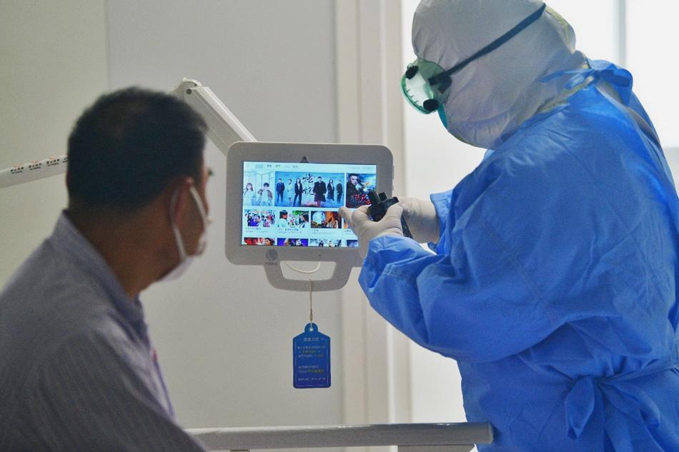 6月16日,北京地坛医院隔离病房内,医护人员教新冠肺炎患者使用平板电脑观看电视节目。人民视觉 图