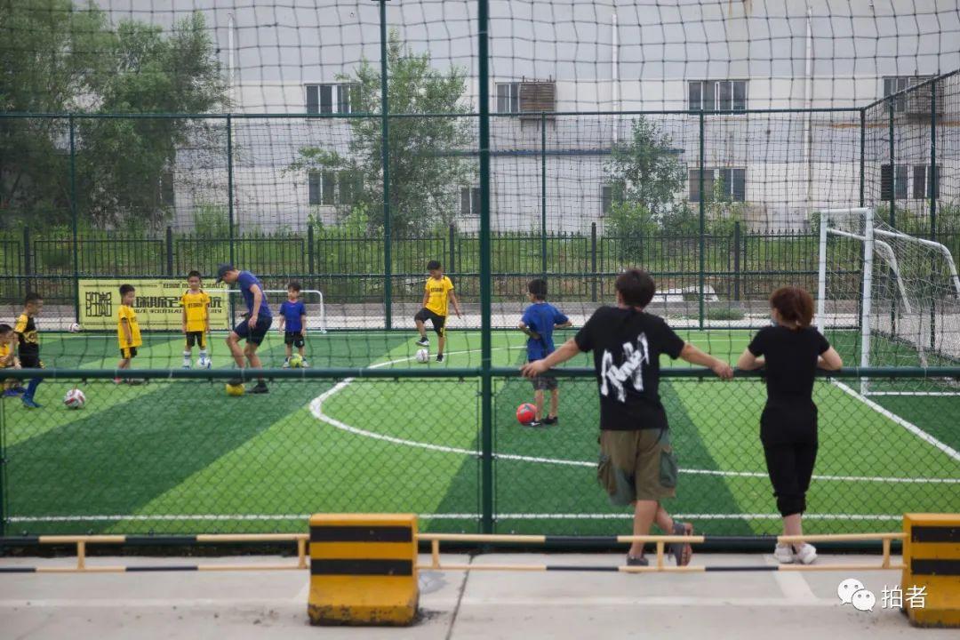 ▲7月11日,河北燕郊,大永與妻子在足球場旁看大兒子上課。