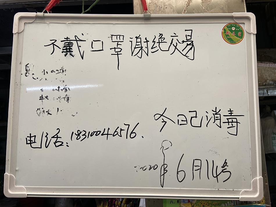 6月14日,北京,丰台区岳各庄批发市场内的商家提示:不戴口罩谢绝交易。人民视觉 图
