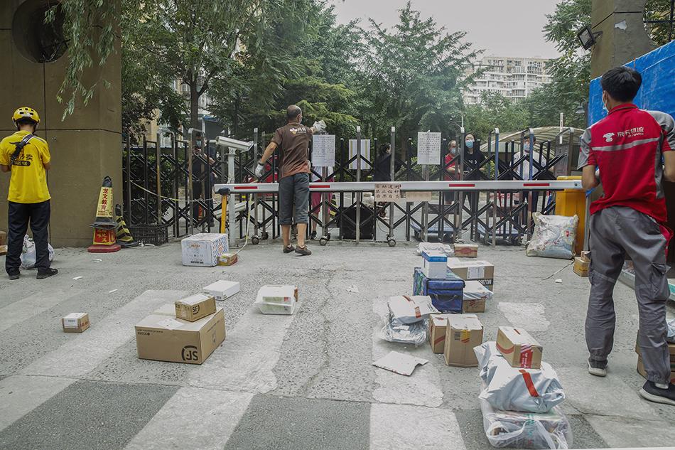 6月17日,快递员在北京市西城区广外街道朗琴园社区外为一位居民递送包裹。张玉薇/新华社 图