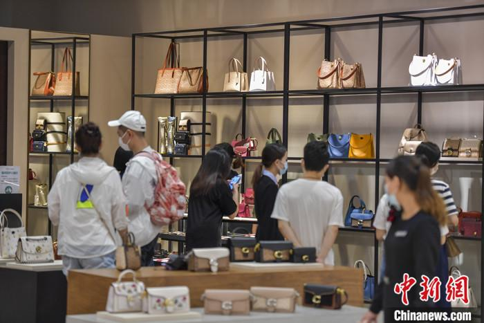 资料图:6月29日,游客在海口日月广场免税店选购免税商品。中新社记者 骆云飞 摄