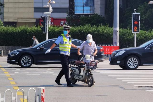 一名骑电动车的非机动车驾驶人因为闯红灯,被交警处罚。郭诚 摄